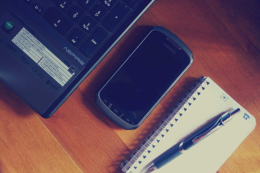 [photo of smartphone on wood desk, nestled between a laptop and a paper notebook]